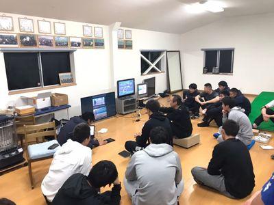 鴻江キャンプ中の夜間、投球動作の比較画像を用いて、自身のフォームの理解に努める選手たち